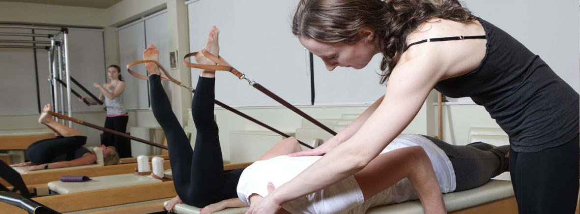 Instructor assists client to achieve good form at Boditree Pilates Vancouver